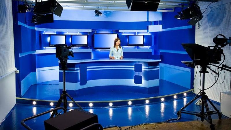 A television studio with cameras, lights, monitors, set and an on-camera person sitting behind the set.