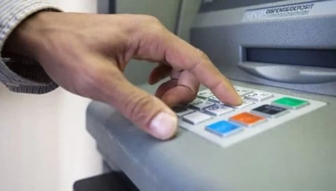 hand pressing the keypad on a ATM machine