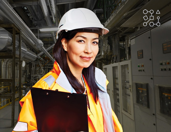 Woman in a hard hat holding a clipboard in a factory