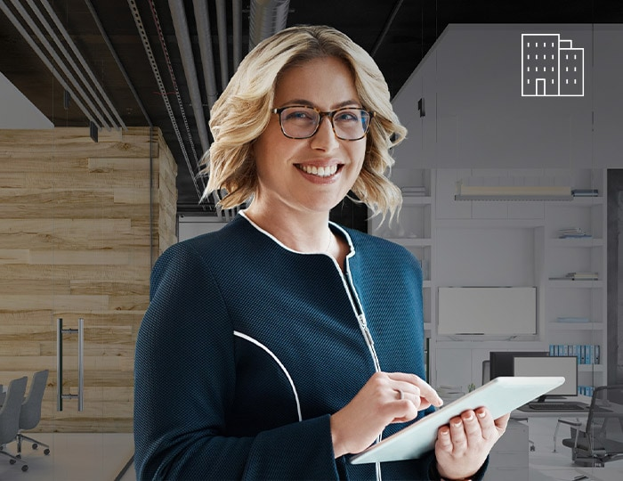 Smiling woman holding a tablet in an office