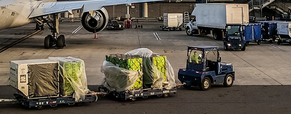 a small car pulling some pallets at an airport