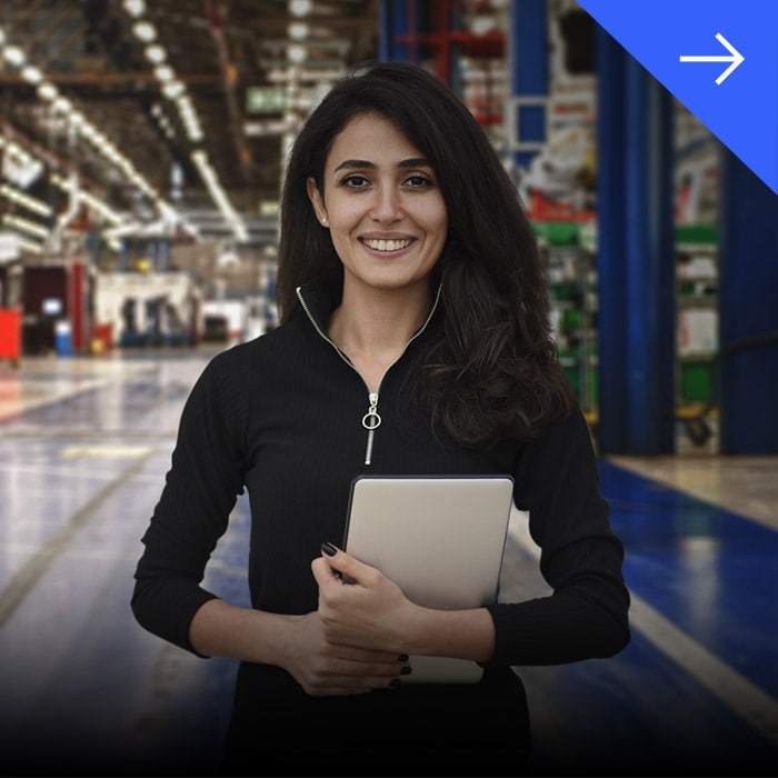 Woman standing in a warehouse holding a tablet