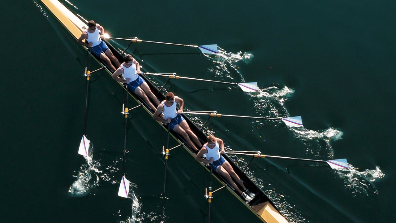 Four-person rowing team skimming across water