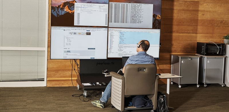 A man uses cloud apps in front of large monitors