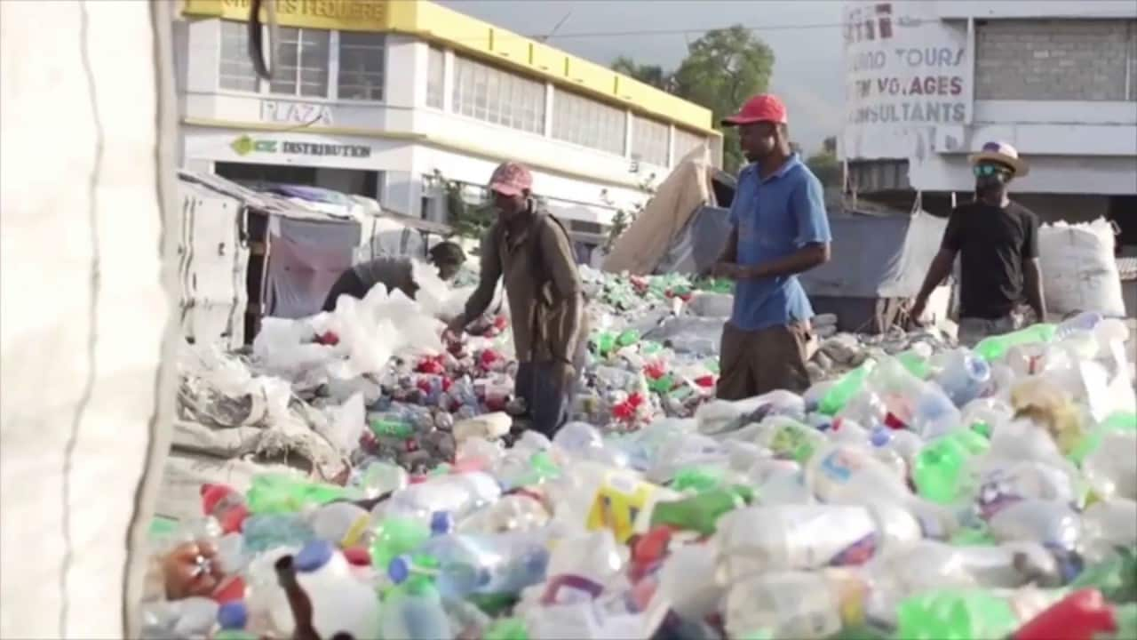 The Plastic Bank people going through trash