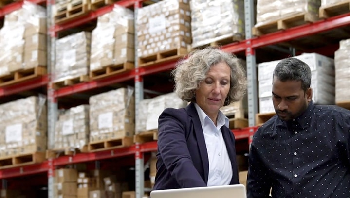 Two people standing in front of stacks of supplies in a warehouse setting