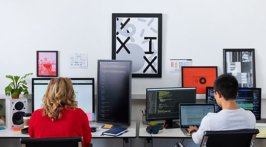 Man and woman working at computers with multiple monitors