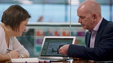 Two people seated in a workplace environment looking at an iPad