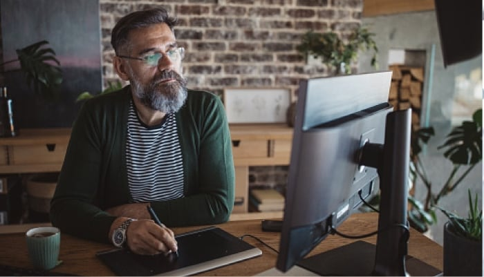 man working from home using desktop computer