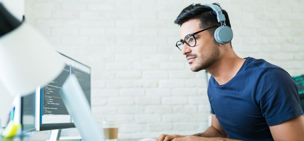 Man with headphones learning at a desktop