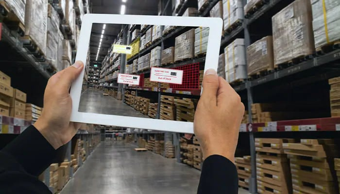 Person inspecting warehouse inventory with an AR-enabled tablet