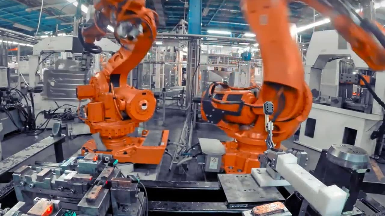 Two orange robotic arms in factory environment