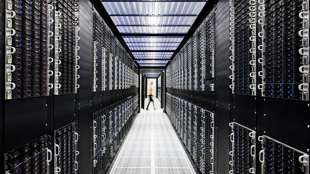 A figure moves past a long row of servers