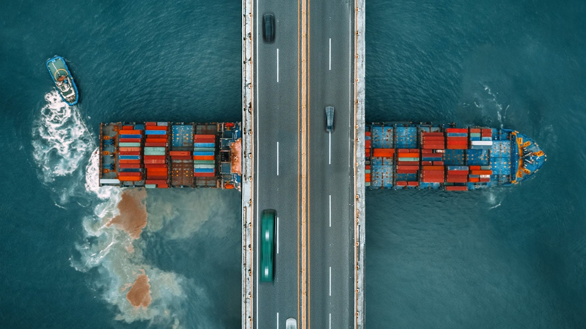 Top view of a ship filled with containers floating under a bridge
