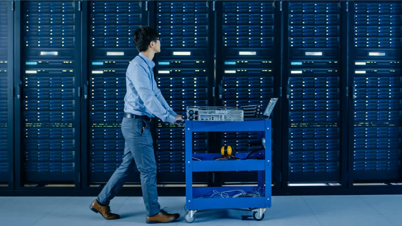 Man in an server room with a cart