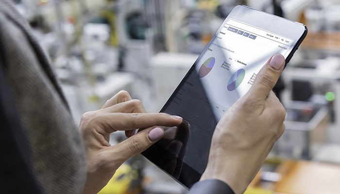 Person accessing a tablet document on a factory floor