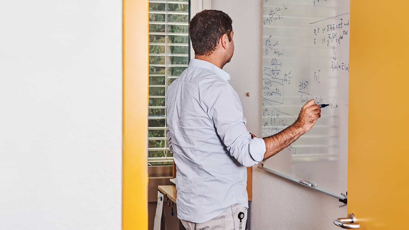 Man writing on a board with a pencil