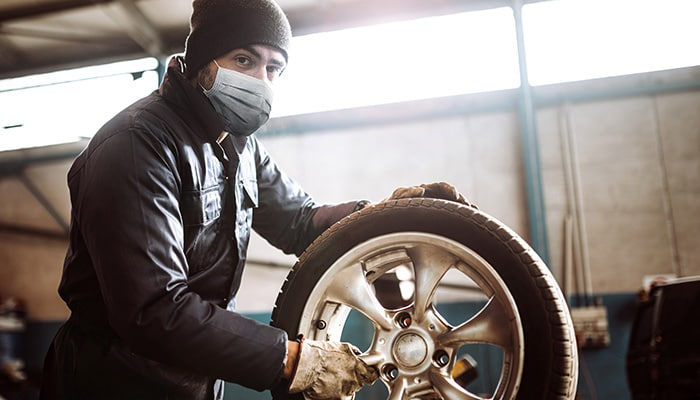 Man wearing personal protective equipment while working on a tire.