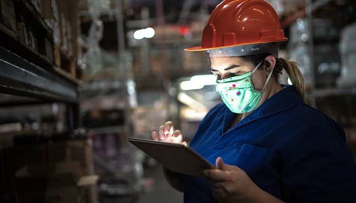 Woman wearing a helmet and mask getting sensor data insights from a tablet in a warehouse.