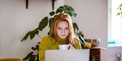 woman holding a coffee cup looking at a laptop computer