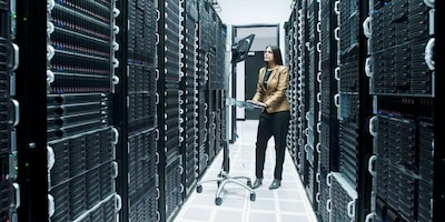 one women inside of a datacenter working on notebook
