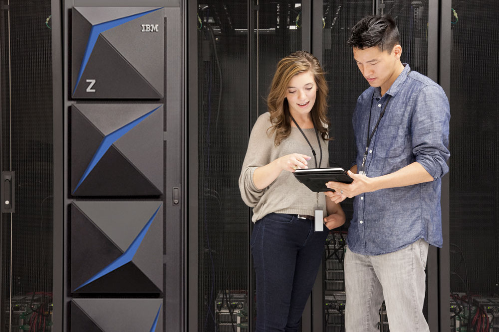 woman and man looking at a tablet next to IBM Z Systems