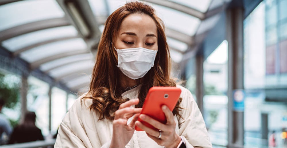Woman wearing face mask using smartphone