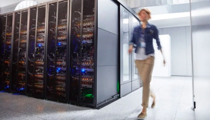 a woman walking beside some computer servers