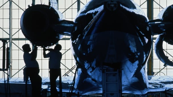 Workers fixing jet engine