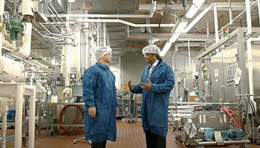 Two men discussing on factory floor