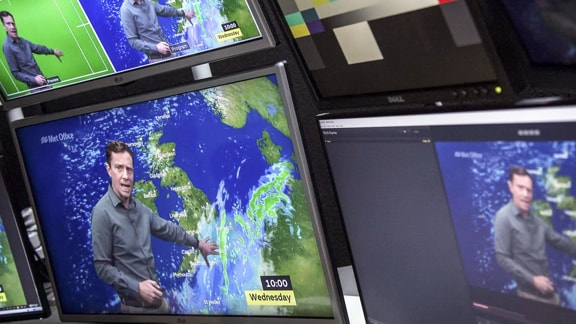 Three TV screens showing weather telecast