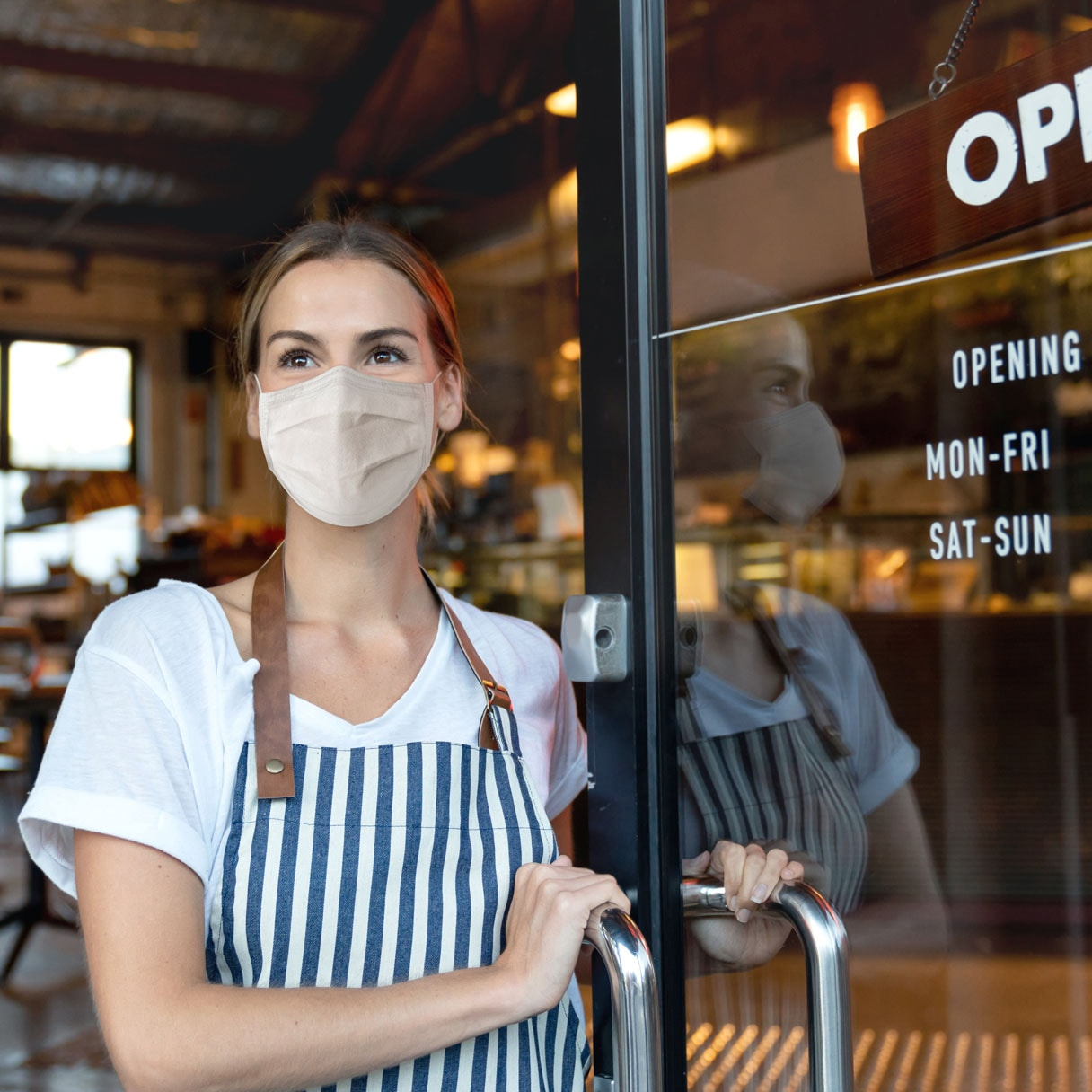 person wearing face mask and apron holding business door open