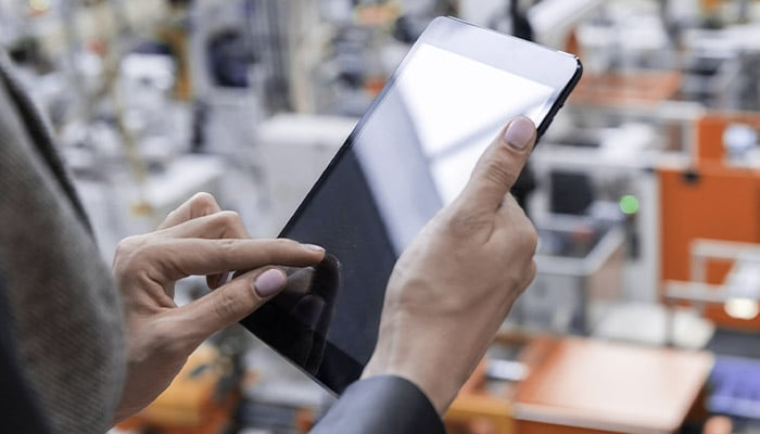 Business person using a tablet on a factory floor