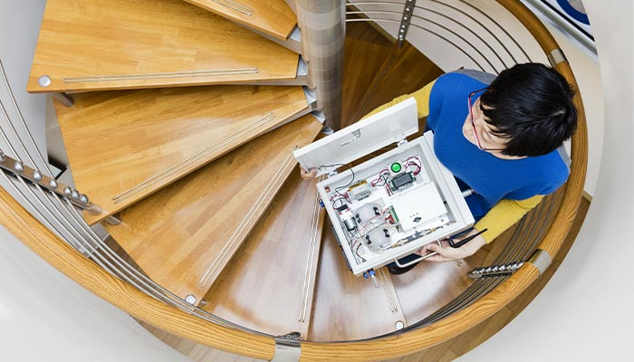 Woman holding a technical systems product design walking up a circular staircase