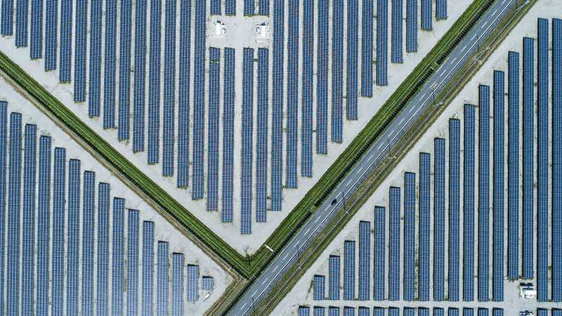 overhead view of a road cutting through solar panel fields