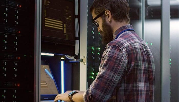 a man typing in the laptop next to servers