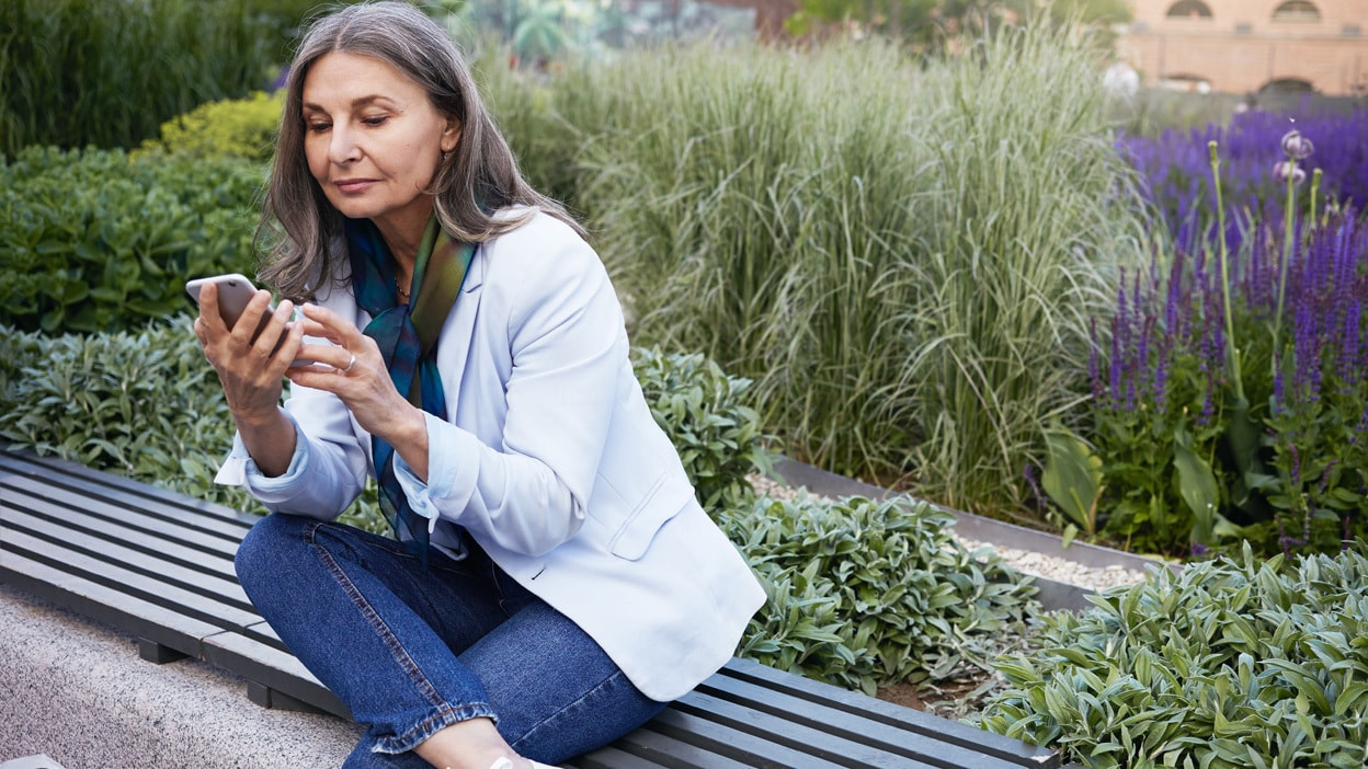 Woman looking at her mobile phone on a bench in a garden