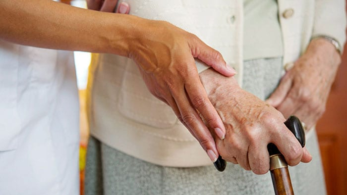 An aid's hand guides an elderly hand holding a cane