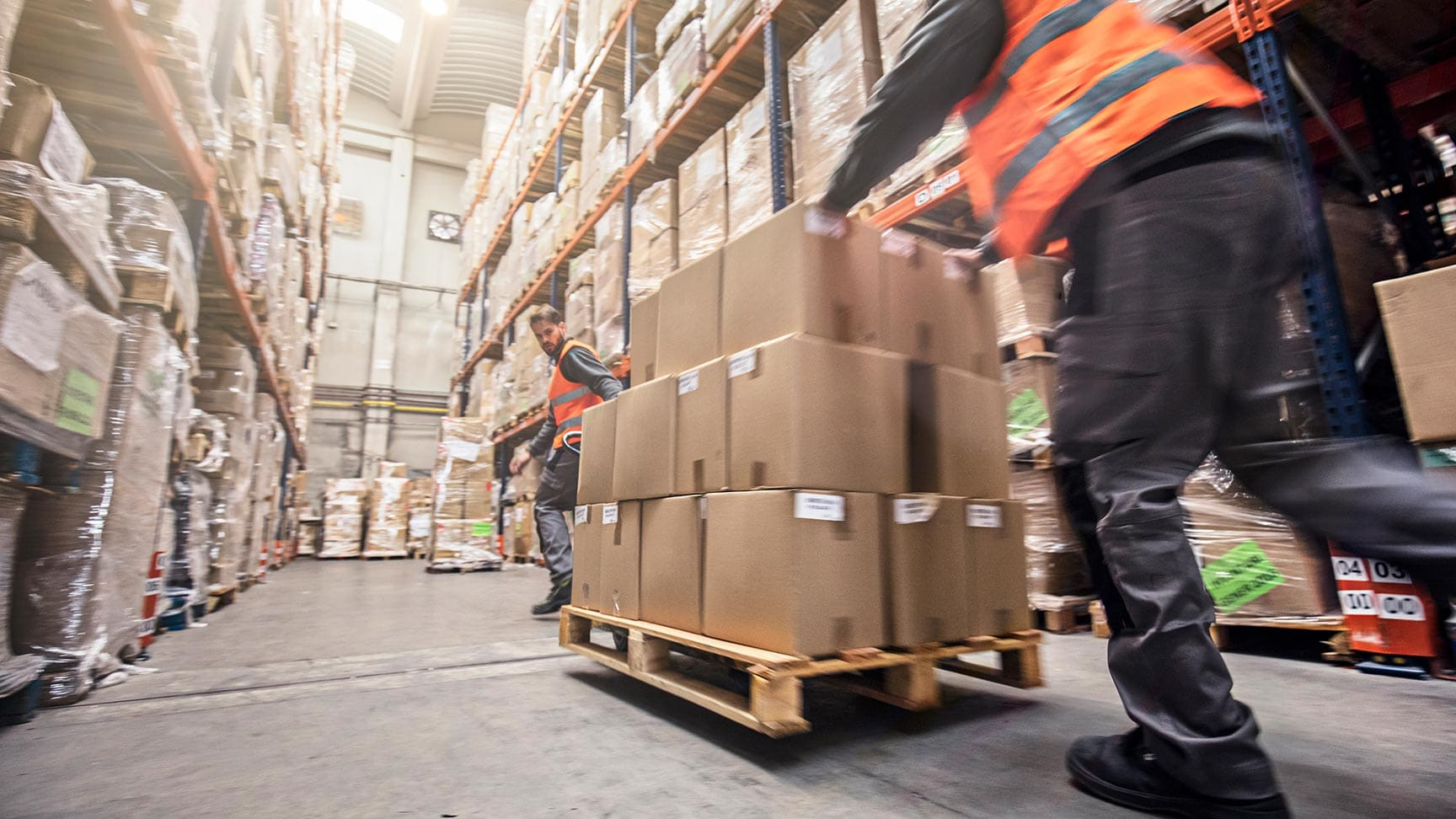 man carrying cargo cart loaded with packages through warehouse