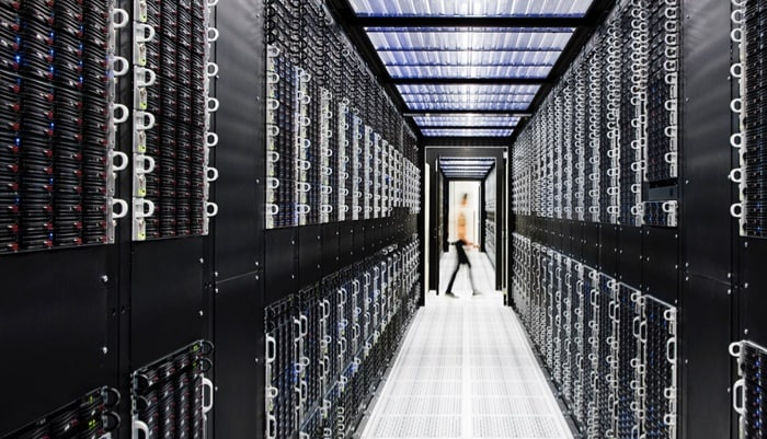 person walking across end of hallway perspective of mainframes