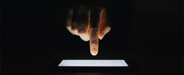 Close-up of a hand over a digital tablet, about to input a selection