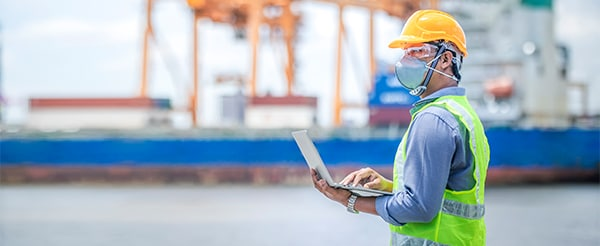 Man about to input data on a digital tablet, next to a container ship