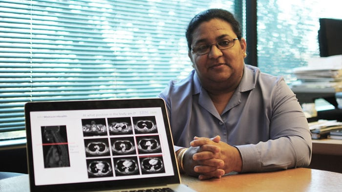 Tanveer sits with a screen displaying images of brain scans