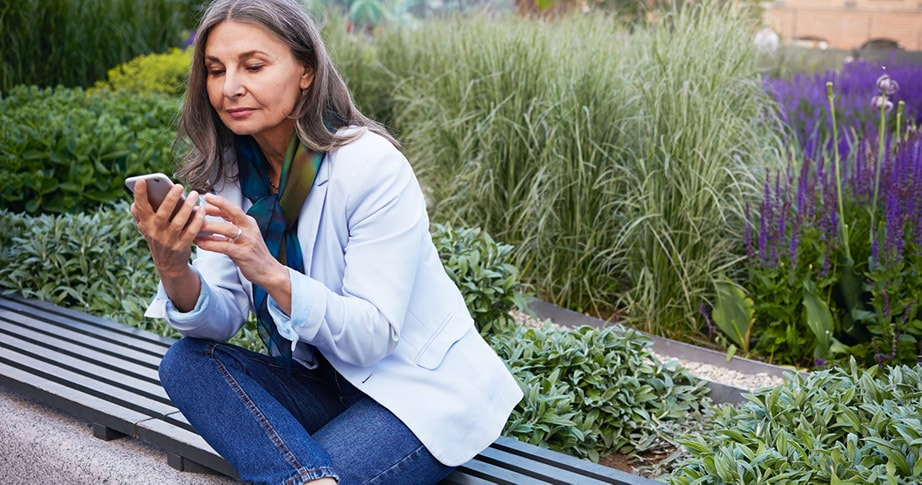 Professional woman sitting on bench with a garden behind her holding a handheld device