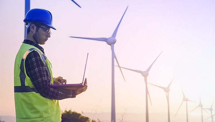 Worker inspecting a laptop at a wind farm