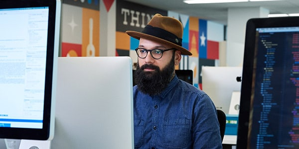 man wearing hat working on a computer