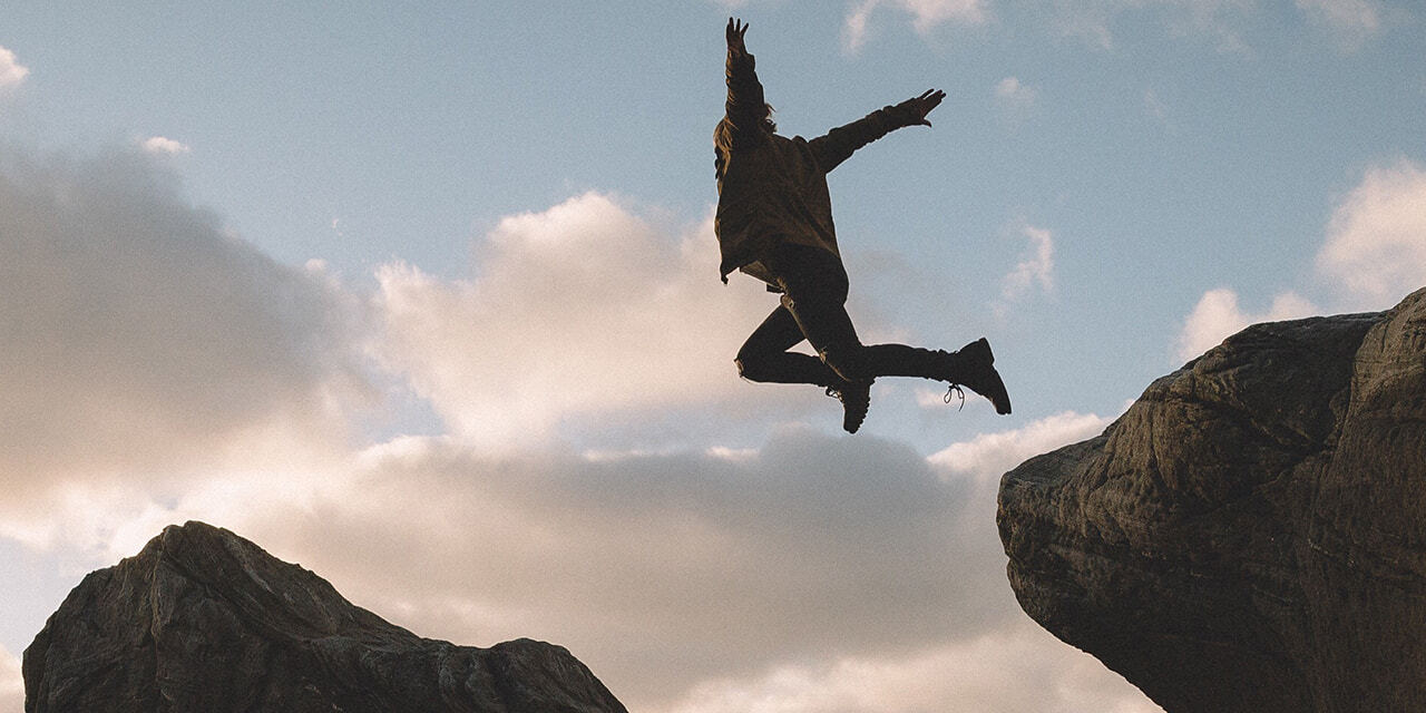 Man jumping from a rock with open arms