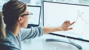 Sideview of woman pointing to one of her desk top screens representing Ordinance Survey