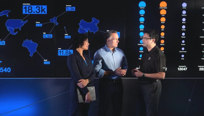 two men and one woman standing talking, with a data panel behind