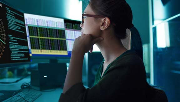 IT expert looking at computer screens